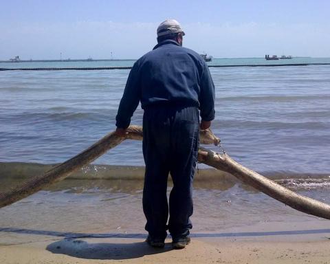 Operaio impegnato in interventi di bonifica di un'area a ridosso della raffineria di Gela